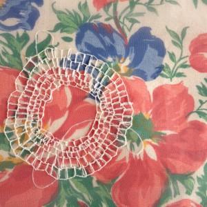 festonroos op doorzichtige stof. Gelegd op een Marker bauwtje met rozen.