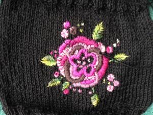 roos in satijnsteek op breiwerk