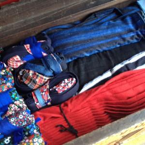 Kist met opgevouwen Staphorster rokken, schorten en kraplappen