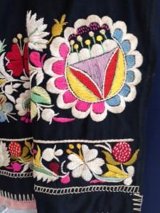 Gekleurd borduurwerk op zwarte schort, vnl. satijnsteek, laddersteek en kettingsteek