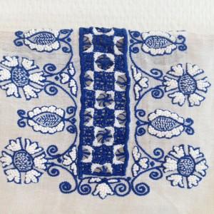 schouderstuk van blouse in blauw/wit met o.a. een vulling van tweekleurig naaldkant en de bloemen in steelsteek en knoopjessteek