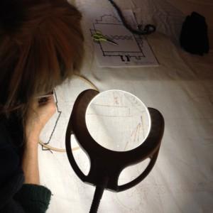 We borduren met de nodige hulpmiddelen als daglichtlamp/loep en kacheltjes onder de tafel.